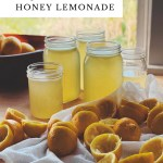 honeyed lemonade in glass jars with halves of juiced lemons resting nearby