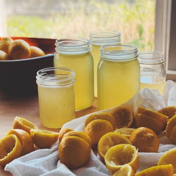 lots of squeezed lemon halves, jars of lemonade, and a bowl of lemons