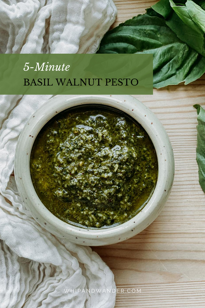 green basil pesto made with walnuts in a light colored dish resting on a wooden surface