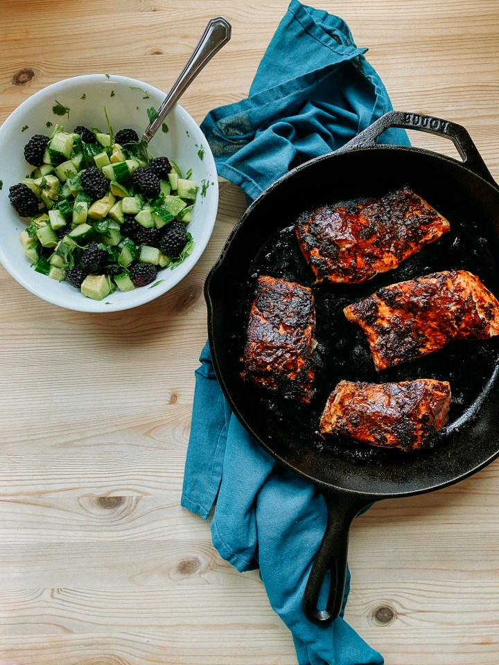 a cast iron pan resting on a blue towel on a wooden table that has spicy salmon adodo and a white bowl with blackberry salsa sitting nearby