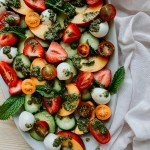 strawberry peach salad on a white platter resting on a white towel