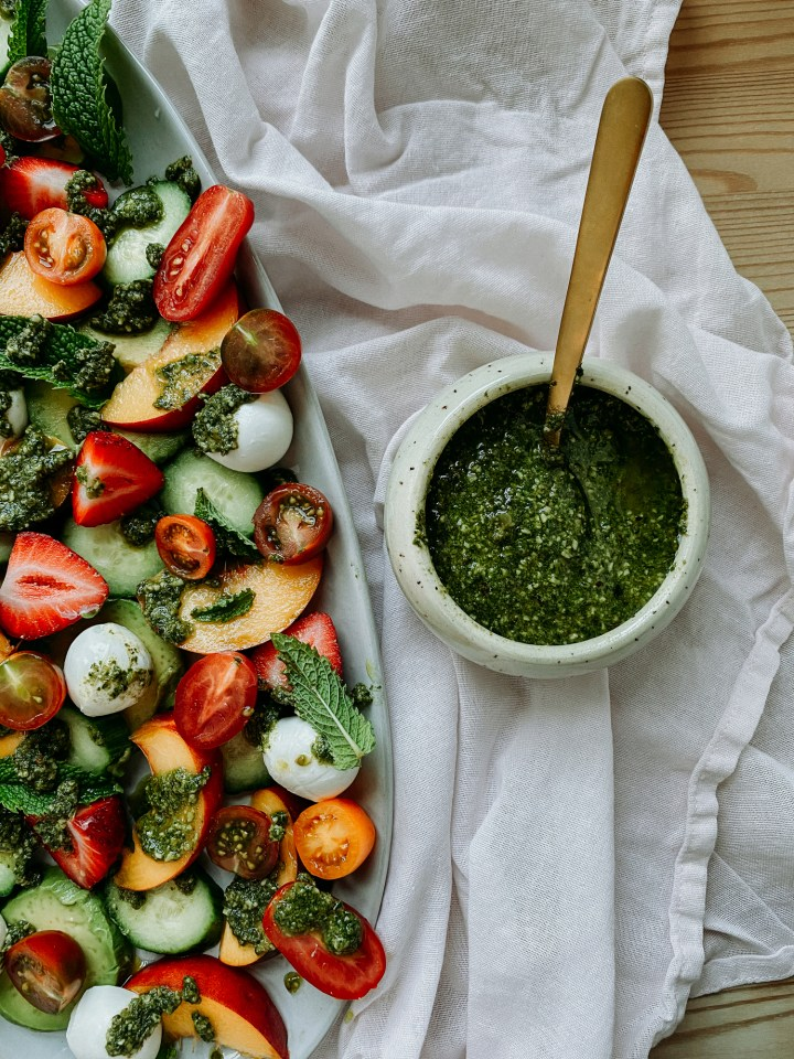 basil walnut pesto in a dish witha gold spoon sitting next to a platter of summer salad with strawberries and peaches
