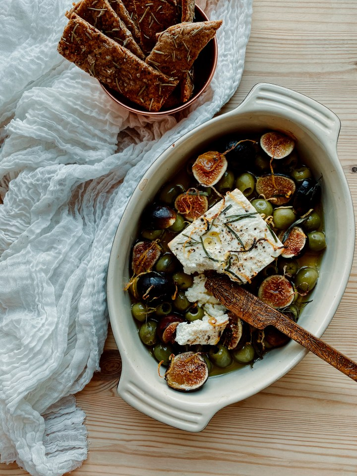 a wooden knife resting in a dish of baked feta, figs, and green olives on a wooden surface. a container of crackers rests nearby on a white towel