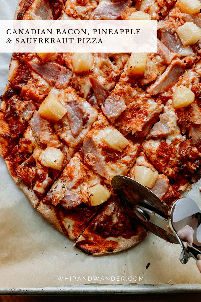 a pizza cutter slicing through a pizza with canadian bacon, pineapple, and sauerkraut