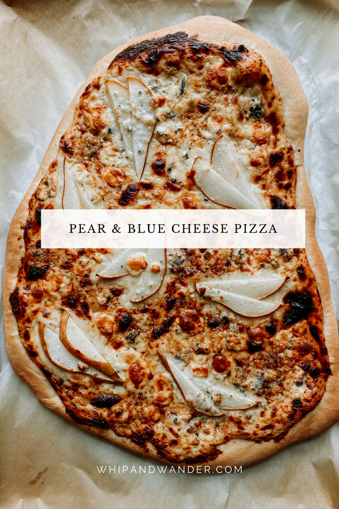 a Pear and Blue Cheese Pizza thats been baked on a sheet of parchment paper on a baking tray