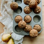 Sourdough Discard Spiced Pear Muffins in a baking tin setting on top of a piece of cheesecloth next to two fresh pears