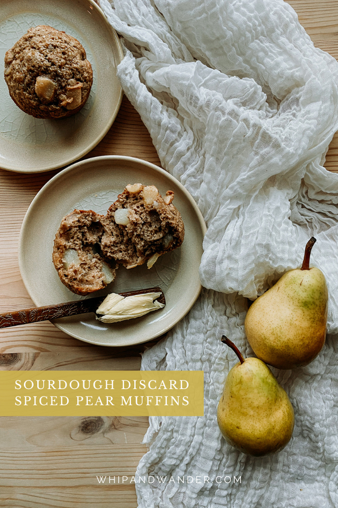 a plate with a Sourdough Discard Spiced Pear Muffins torn in half and a wooden knife with butter resting on the plate next to neutral cloth with two pears resting on top