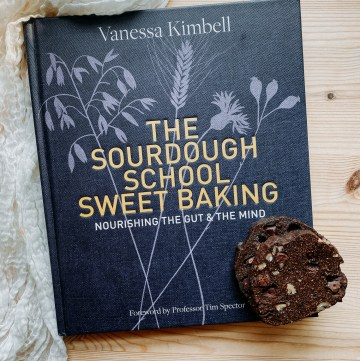 a photo of the cookbook The Sourdough School: Sweet Baking: Nourishing the Gut & the Mind on a wooden surface with a stack of cookies resting on top