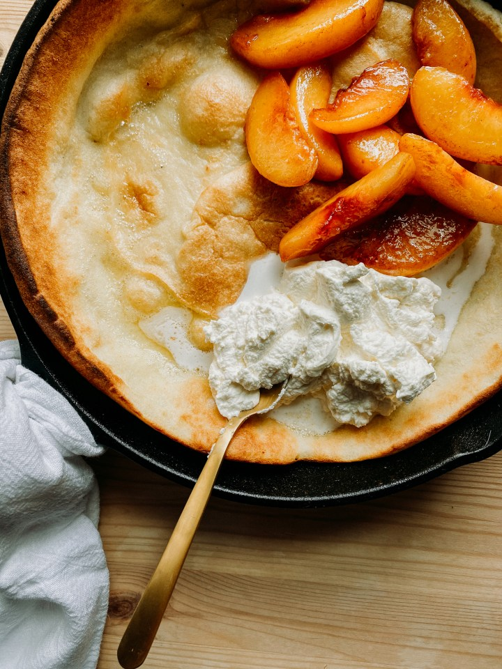 a gold spoon resting in a pile of whipped cream next to peaches on top of a Buttermilk Dutch Baby in a cast iron skillet