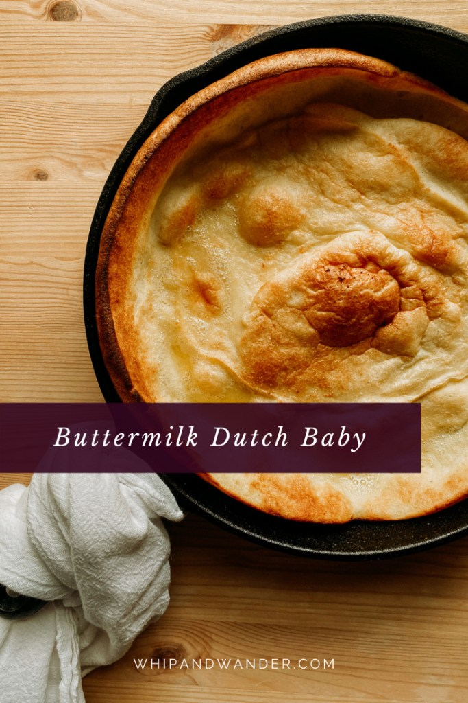 a white twoel wrapped around the handle of a cast iron pan containing a Buttermilk Dutch Baby