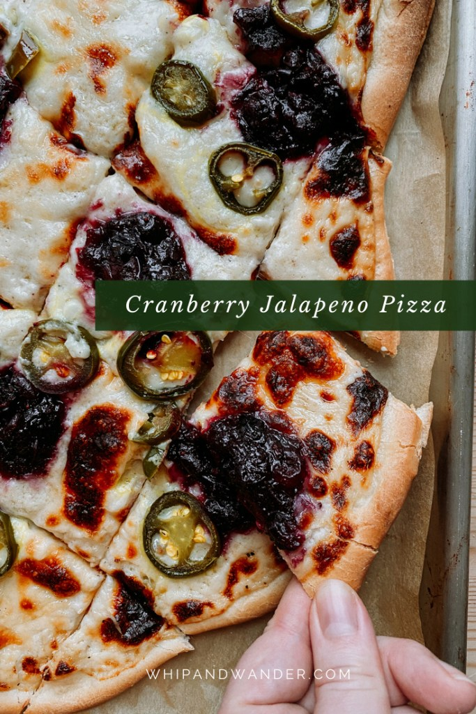 a hand pulling a square slice of cranberry jalapeno pizza from a large pizza on a baking sheet