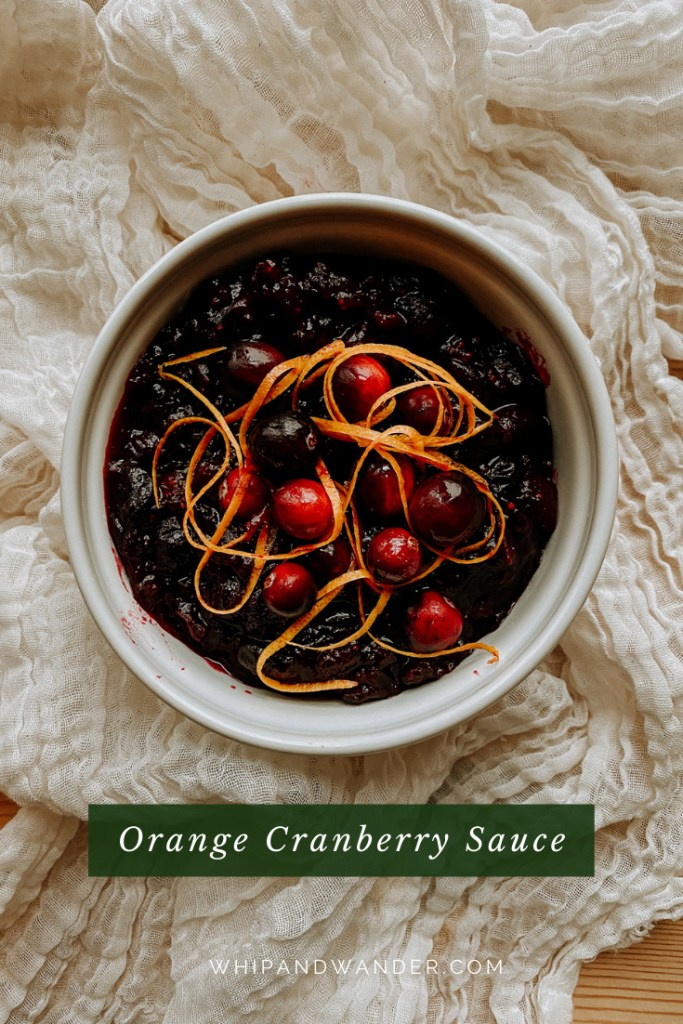 swirls of orange zest and fresh cranberries topping a white dish of orange cranberry sauce resting on a cloth