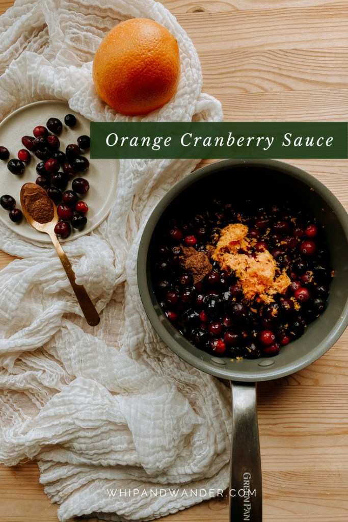 a medium saucepan with the makings of orange cranerriy sauce in it resting on a white cloth next to a plate of cranberries and cinnamon and a whole orange