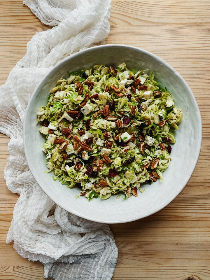 Shaved Brussels Sprouts Salad with Blue Cheese, Cranberries, and Pecans in a white bowl resting on top of a white cloth on a wooden table