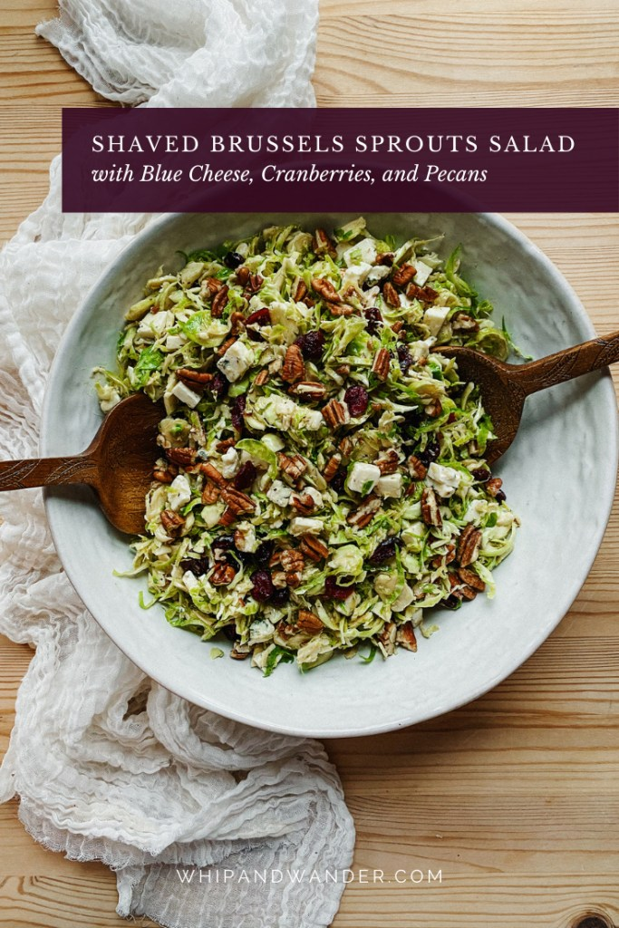 two wooden serving utensils resting in a white dish of Shaved Brussels Sprouts Salad with Blue Cheese, Cranberries, and Pecans