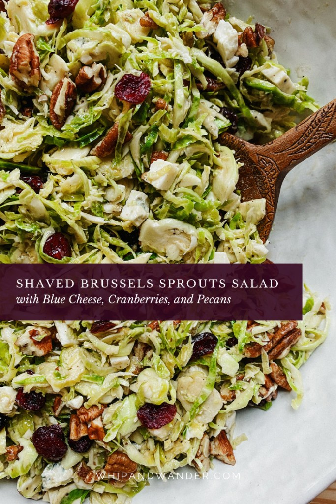 Shaved Brussels Sprouts Salad with Blue Cheese, Cranberries, and Pecans in a white bowl with a wooden spoon resting in the salad