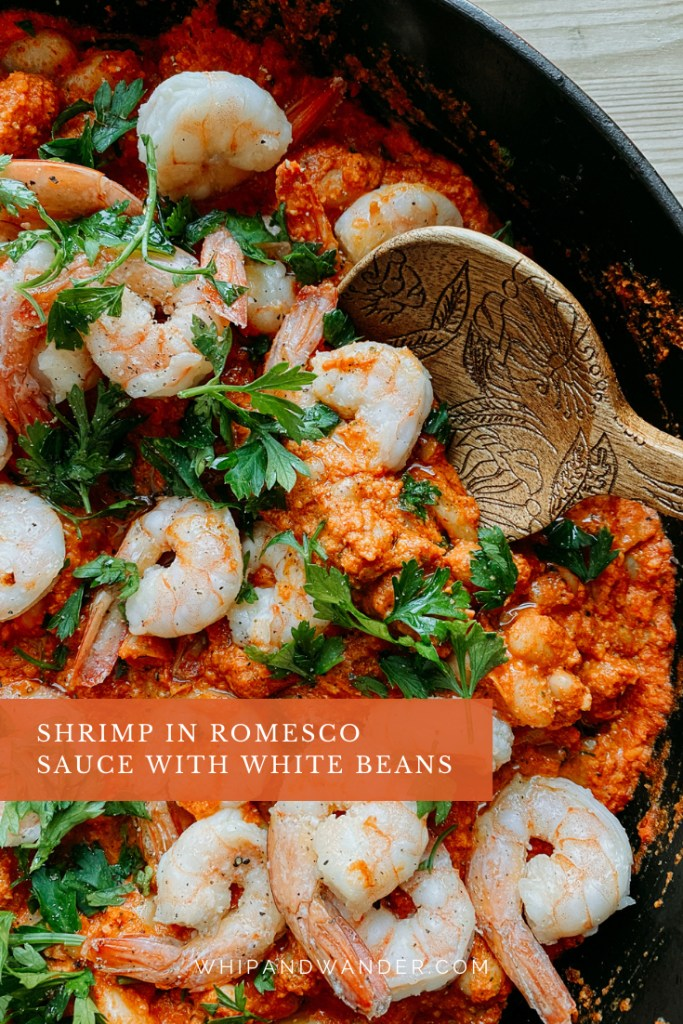 a spoons scooping into a dish of shrimp in romesco sauce with parsley and white beans