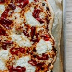 a side view of White Pizza with Hot Pickled Peppers and Honey resting on a baking sheet on a wooden surface