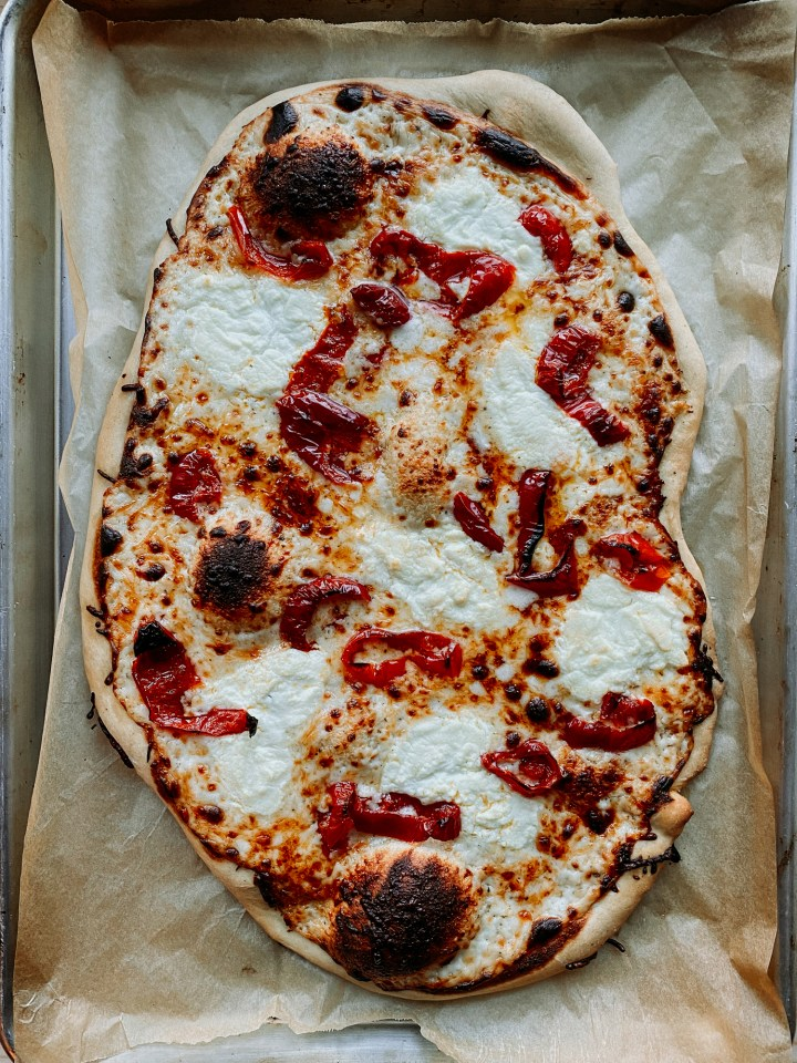 a White Pizza with Hot Pickled Peppers right out of the oven, resting on it's parchment lined baking tray