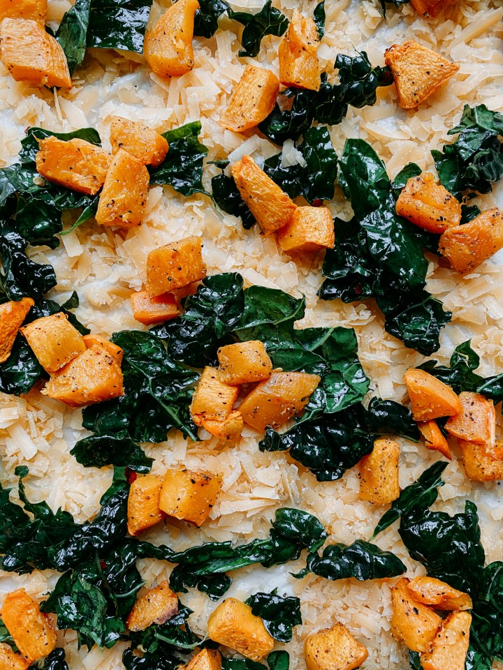closeup of pumpkin, kale, and gouda on an unbaked pizza crust