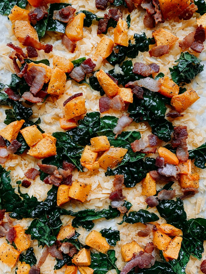 bacon, kale, gouda, and pumpkin on top of an unabaked pizza crust
