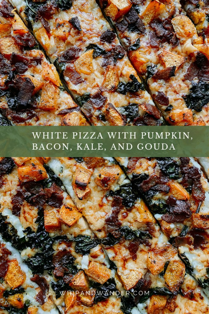 a pizza topped with white sauce, roasted pumpkin, kale, gouda, and bacon and then sliced into diagonal strips