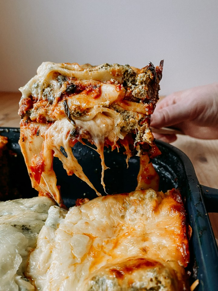 a hand serving a square of melty cheesy Christmas Eve Lasagna from a casserole dish