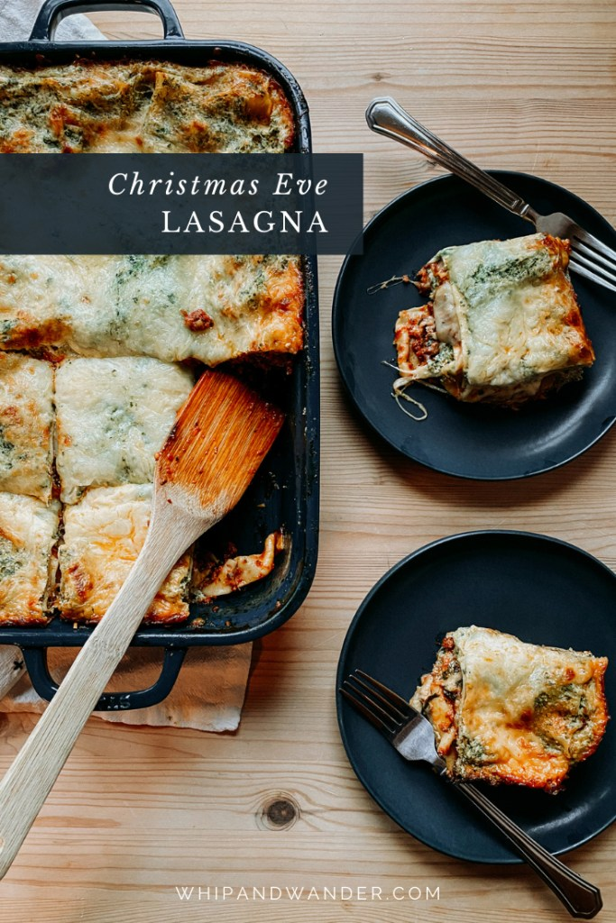 a wooden spatula resting in a pan of Christmas Eve Lasagna with two dark blue green pates resting nearby on a wooden surface