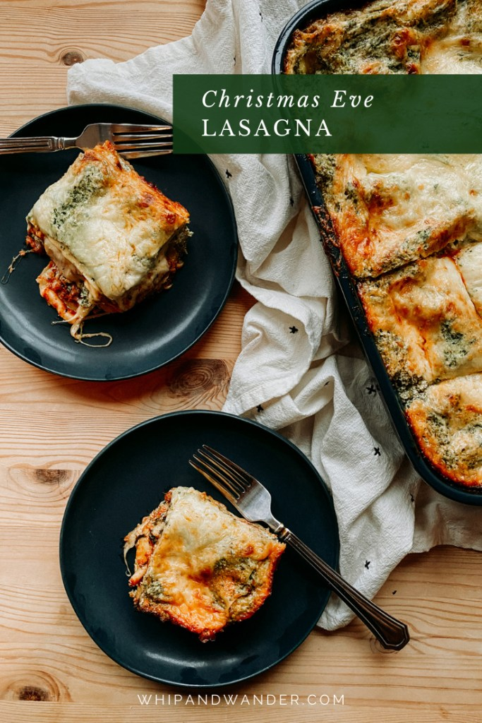 two dark blue green plates with squares of Christmas Eve Lasagna on top of them resting next to a large pan of lasagna on a towel lined wooden surface