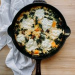 Fall Frittata with Sausage, Butternut Squash, and Kale in a cast iron pan resting ona. white towel on a light wooden surface