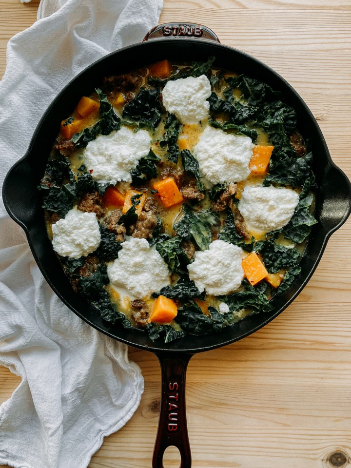 an unbaked frittata with butternut squash, sausage, kale, and ricotta in a cast itorn pan