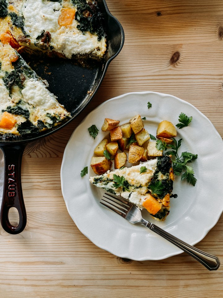 Fall Frittata with Sausage, Butternut Squash, and Kale and potatoes on a white plate with a forn resting next to a cast iron pan filled with frittata