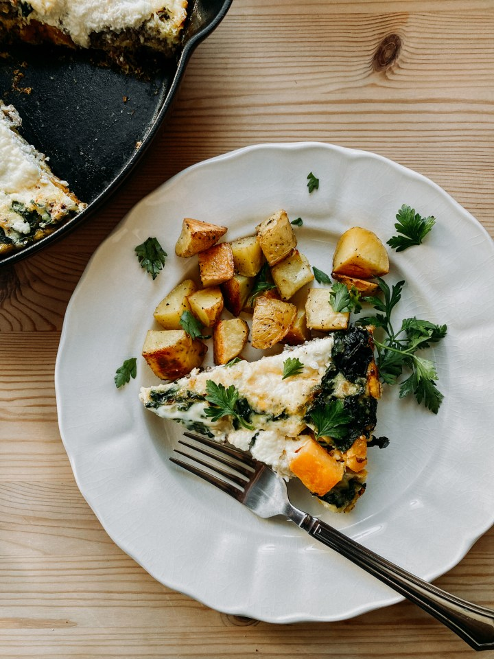 a fork resting on a white plate that contains Fall Frittata with Sausage, Butternut Squash, and Kale and potatoes