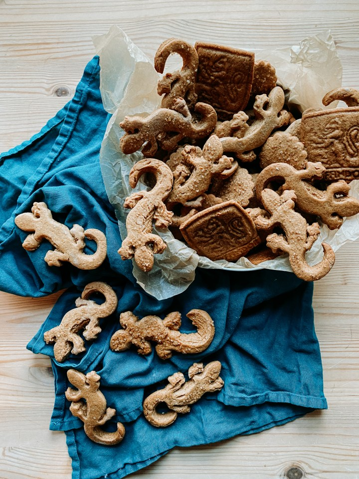 a parchment lined biscuit tin filled with Professor McGonagall's Ginger Newt Biscuits resting on top of a teal towel with additional ginger biscuits on the towel