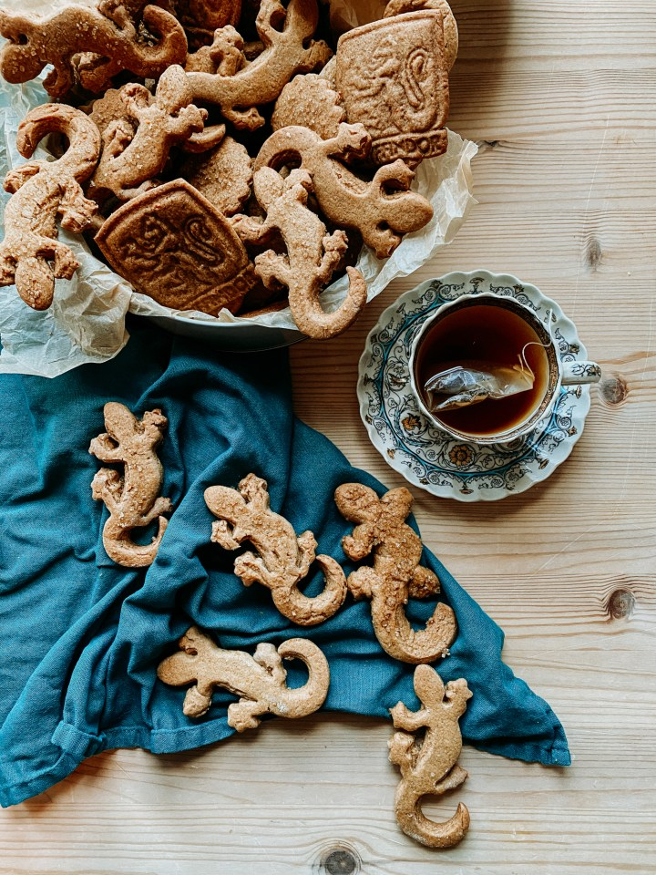 Professor McGonagall's Ginger Newt Biscuits in a tin and on a dark teal twel resting next to a tea cup on a saucer