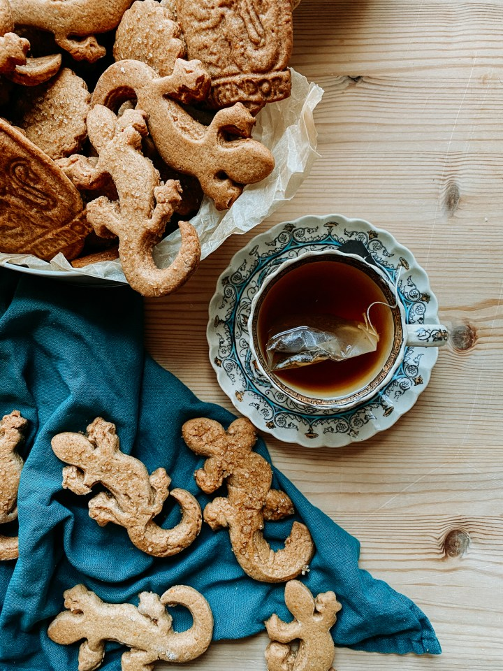 a tea cup on a saucer next to a tin filled with Professor McGonagall's Ginger Newt Biscuits and several more newt biscuits resting on a teal towel