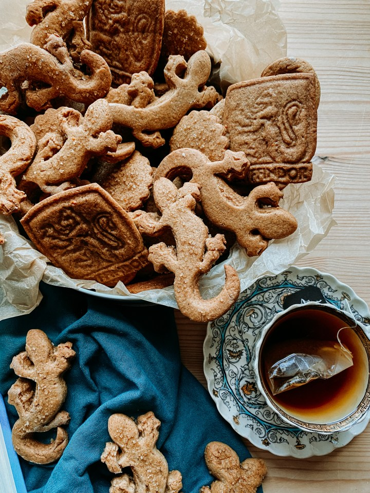 a cookie tin filled with Professor McGonagall's Ginger Newt Biscuits and a cup of tea on a saucer and a dark teal towel with biscuits scattered on top
