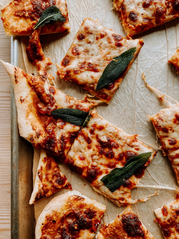 irregular shaped slices of Pumpkin Pizza with Gruyere and Crispy Sage on a baking sheet