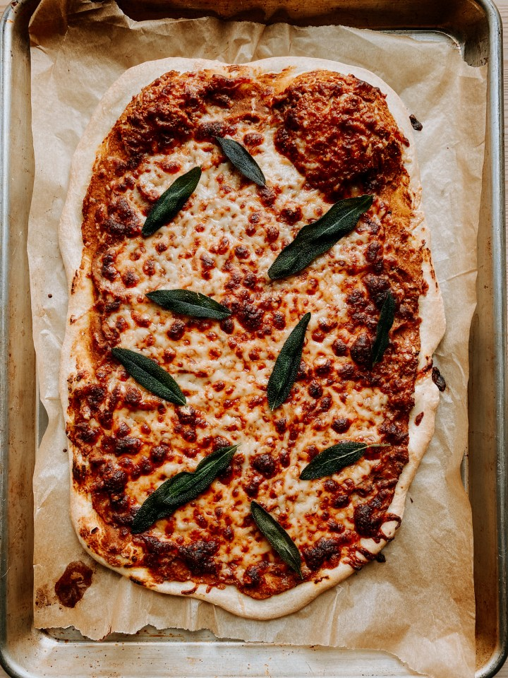 a pizza with blistered cheese and crispy sage fresh out of the oven resting on a parchment lined baking sheet