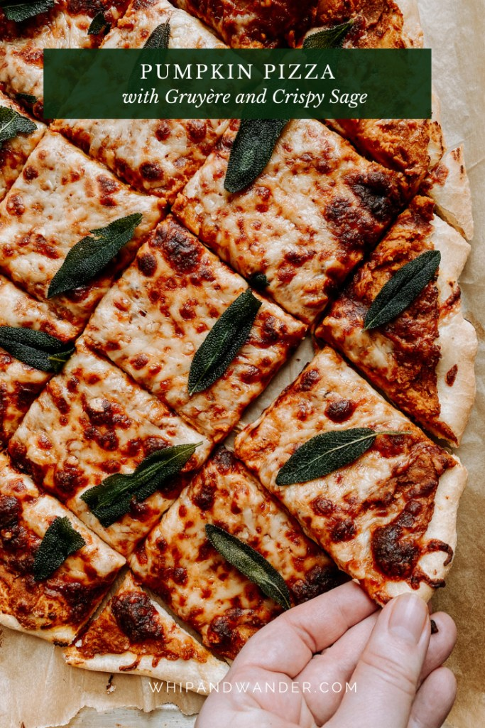 a slice of pumpkin pizza with sage being pulled away from a whole pie by a hand