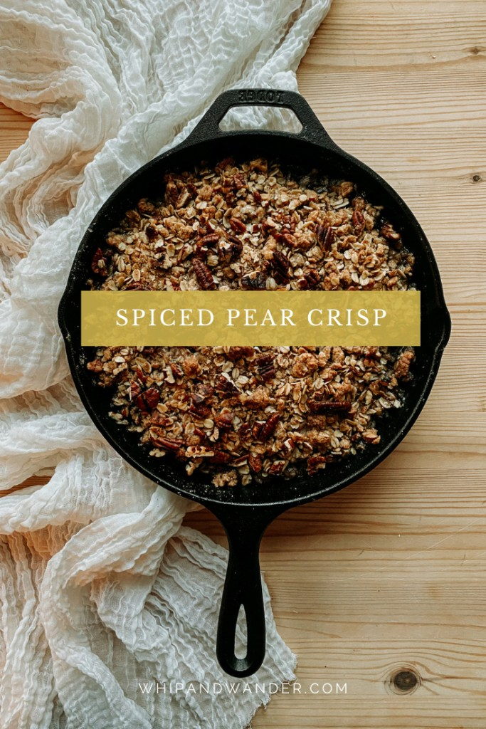 a cast iron pan of Spiced Pear Crisp resting on a cream colored fabric on a wooden surface