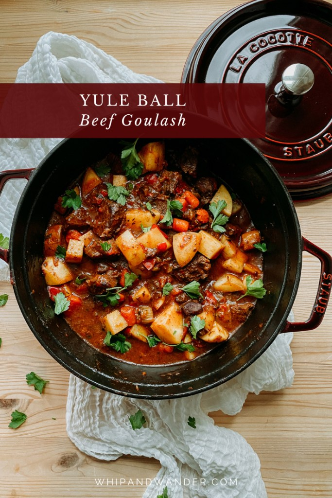a large dutch oven filled with Yule Ball Beef Goulash ona. wooden surface with white cloth and the dutch oven lid