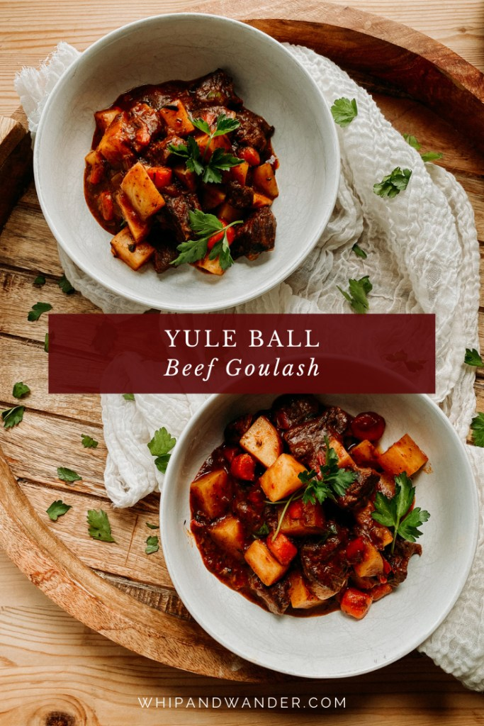 two white bowls filled with Yule Ball Beef Goulash topped with parsley on a wooden round shaped tray