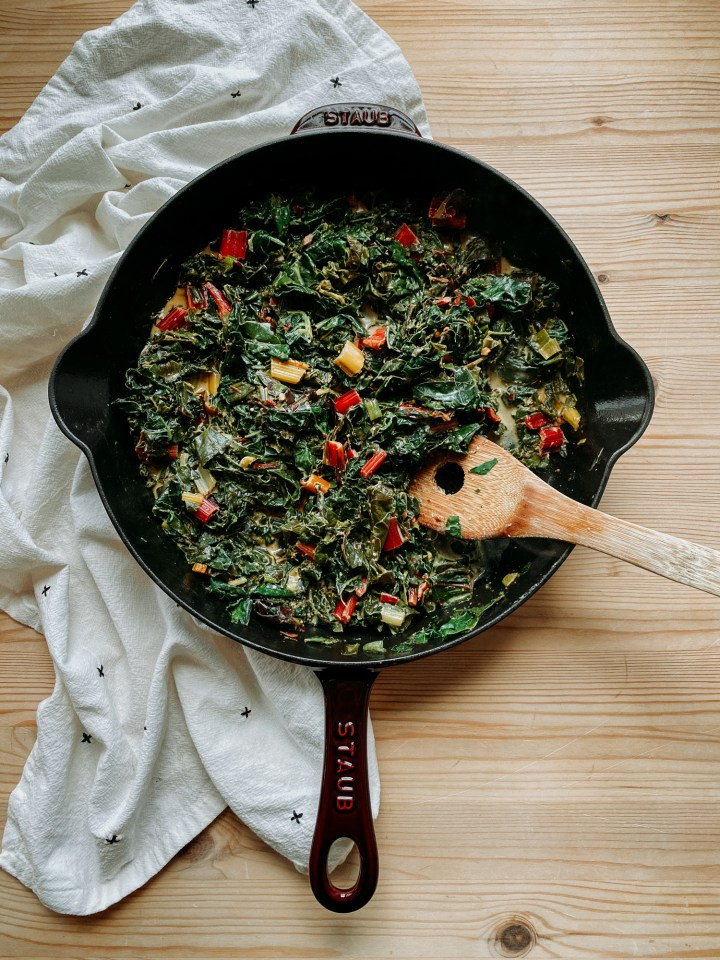Dijon Creamed Greens in a large cast iron skillet with a wooden spoon resting in the pan