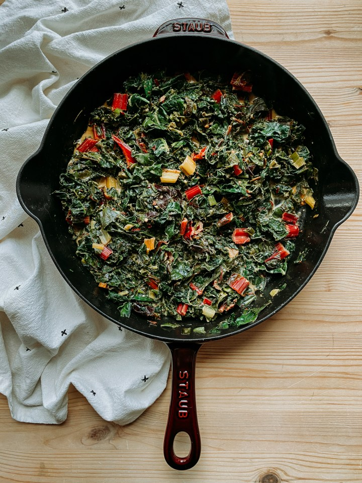 a skillet filled with Dijon Creamed Greens resting on a white towel on a wooden surface