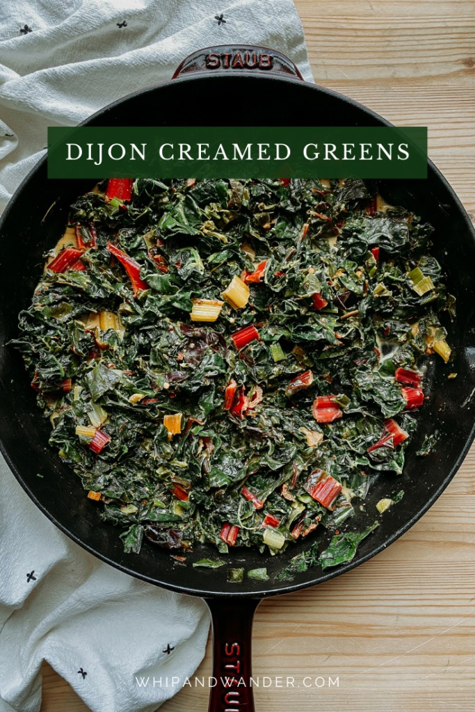 Dijon Creamed Greens in a skillet resting on a surface made of wood with a white and black towel under the pan