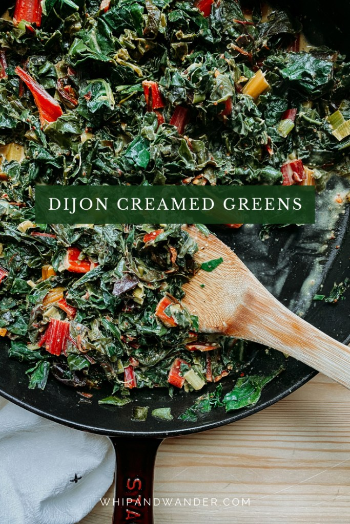a wooden spatula resting in a cast iron pan of greens that have been creamed