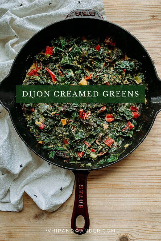 kale and swiss chard that have been creamed in a cast iron pan resting on a wooden surface with a white towel