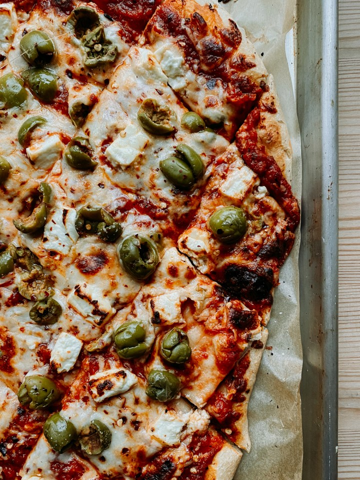 a parchment lined baking sheet topped with a pizza with feta cheese and green olives and res sauce