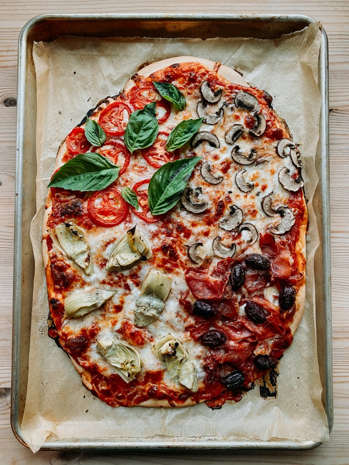 a Pizza Quattro Stagioni fresh out of the oven on a brown parchment lined baking sheet
